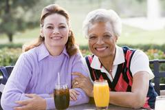 Two female friends enjoying a beverage by a golf course Stock Photos
