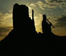 Native American playing flute with Monument Valley sunrise Stock Footage