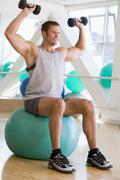 man using hand weights on swiss ball at gym - stock photo