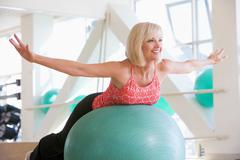 Woman balancing on swiss ball Stock Photos