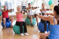 Instructor taking exercise class at gym Stock Photos