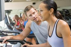 Personal trainer encouraging woman using treadmill at gym Stock Photos