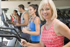 woman running on treadmill at gym - stock photo