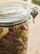 jar of multi-coloured pasta - stock photo