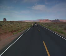Men on motorcycles ride on Monument Valley highway in Utah - stock footage