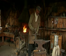 old West blacksmith works with anvil - stock footage