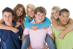 Stock Photo of teenage girls piggy back on boys