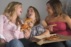 Teenage girls eating pizza Stock Photos