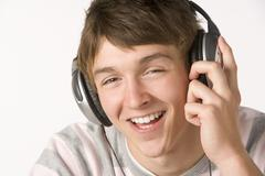 teenage boy listening to music on headphones - stock photo
