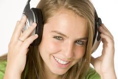 teenage girl listening to music on headphones - stock photo
