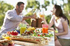 Couple Dining Al Fresco, Toasting Each Other Stock Photos