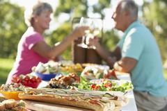 Couple Dining Al Fresco, Toasting Each Other - stock photo