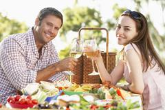 Couple Eating An Al Fresco Meal, Toasting With Wineglasses - stock photo