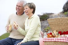 Couple Eating An Al Fresco Meal At The Beach - stock photo