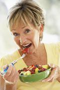 Senior Woman Eating Fresh Fruit Salad Stock Photos