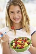 Young Girl Eating Fresh Fruit Salad Stock Photos