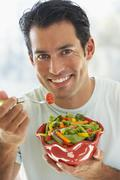 Mid Adult Man Eating Salad - stock photo