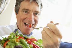 Senior Man Eating Salad Stock Photos