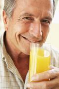 Senior Man Smiling At Camera And Drinking Orange Juice - stock photo