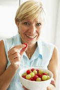 Middle Aged Woman Eating A Bowl Of Fruit - stock photo