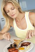 Mid Adult Woman Eating epäterveellinen aamiainen - stock photo
