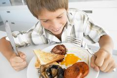 Young Boy Eating Unhealthy Fried Breakfast - stock photo