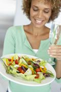 Mid Adult Woman Holding A Wine Glass And Fresh Salad - stock photo