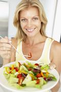 Mid Adult Woman Eating A Healthy Salad - stock photo