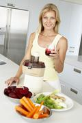 Mid Adult Woman Making Fresh Vegetable Juice - stock photo