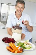 Middle Aged Man Making Fresh Vegetable Juice Stock Photos