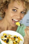 Mid Adult Woman Eating Fresh Fruit Salad - stock photo