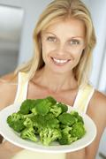 Mid Adult Woman Holding A Plate Of Broccoli - stock photo