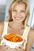 Mid Adult Woman Holding A Bowl Of Carrots - stock photo