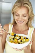 Mid Adult Woman Eating A Bowl Of Fresh Fruit Stock Photos