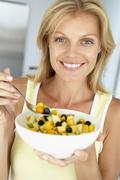 Mid Adult Woman Eating A Bowl Of Fresh Fruit - stock photo