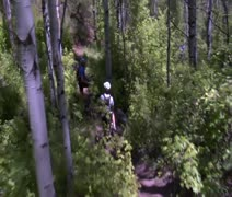 Mountain bikers pedal down steep wooded trail Stock Footage