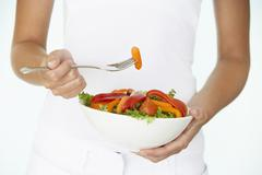 Young Woman Holding Bowl Of Salad - stock photo
