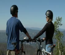 Mountain biking couple pause for view Stock Footage