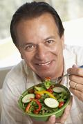 Middle Aged Man Eating Salad - stock photo