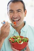 Middle Aged Man Eating A Fresh Green Salad - stock photo