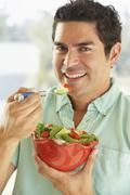 Mid Adult Man Holding A Bowl Of Salad, Smiling At The Camera - stock photo