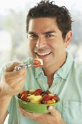 Mid Adult Man Holding A Bowl Of Fresh Fruit Salad Smiling At The Camera - stock photo