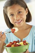 Girl Eating A Bowl Of Fresh Fruit Salad - stock photo