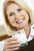 Senior Woman Holding A Glass Of Milk, Smiling At The Camera Stock Photos