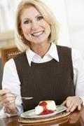 Senior Woman Eating Cheesecake - stock photo