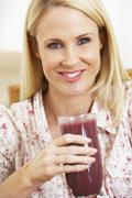 Mid Adult Woman Holding A Fresh Berry Smoothie - stock photo