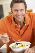Middle Aged Man Eating A Healthy Meal, Smiling At The Camera - stock photo