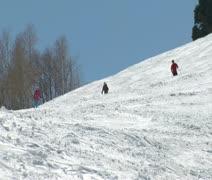 Skiiers plunge down tough terrain on bluesky day Stock Footage