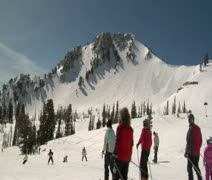 Many skiiers glide down mellow hill, blue sky - stock footage
