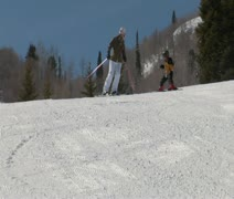 Mom leads little kid down gentle ski slope Stock Footage